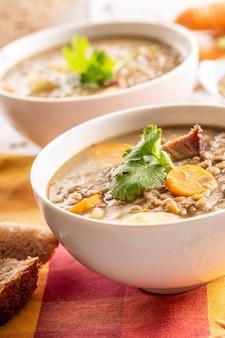 スモークポークネック、ニンジン、ジャガイモ、コリアンダーのレンズ豆のスープ。伝統的なスロバキア料理、チェコ料理、または東ヨーロッパ料理。