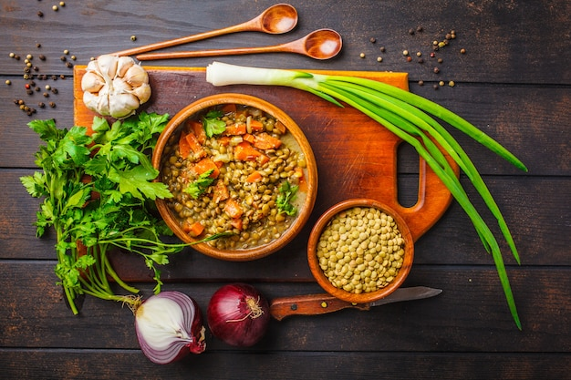 Lentil soup in a wooden bowl and ingredients on a white wooden background, top view.