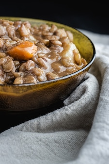 Lentil stew in bowl with vegetable. close-up.