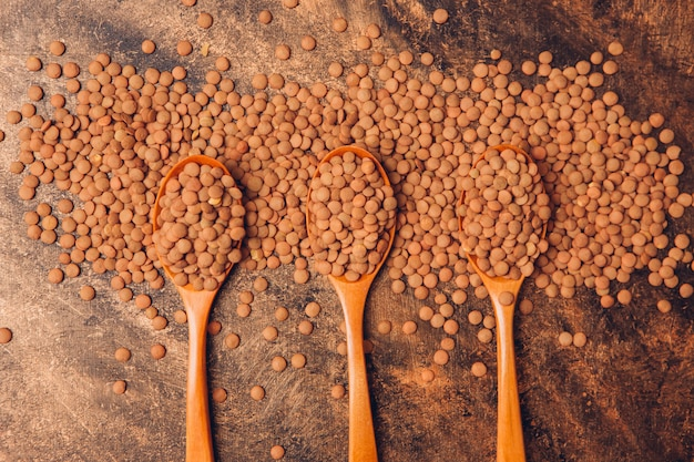 Lentils on 3 wooden spoons with top view on a wooden table