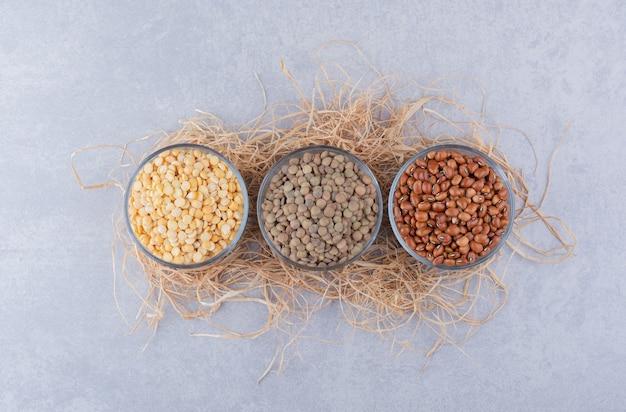 レンズ豆と小豆は大理石の表面のわらの山の上のガラスのボウルに分けられました