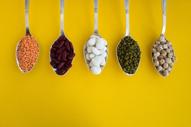 黄色の背景のスプーンでレンズ豆、豆、緑豆、ひよこ豆。上面図。コピースペース。