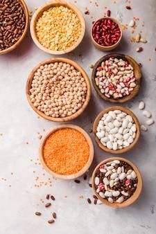 白い石のテーブルトップビューで別のボウルにレンズ豆、チークエンドウ、豆の品揃え。