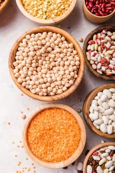 白い石のテーブルの上の別のボウルにレンズ豆、チクピース、豆の品揃え。