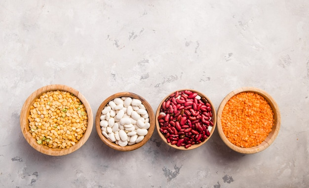 Lentils, chikpea and beans assortment in different bowls on white stone  table .