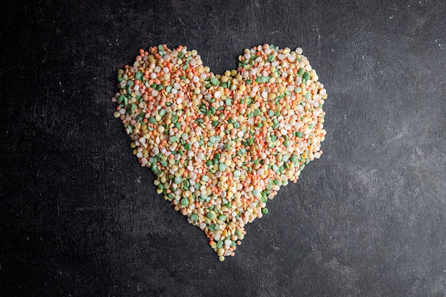 Lentils forming heart shape top view on a dark textured background