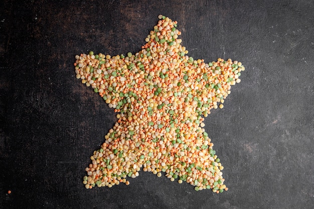 Lentils forming star shape on a dark textured background. top view.