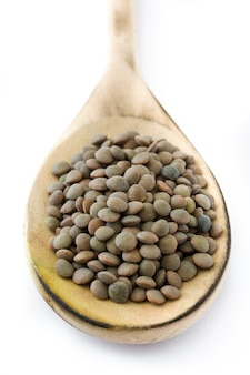 Lentils grain on wooden spoon isolated
