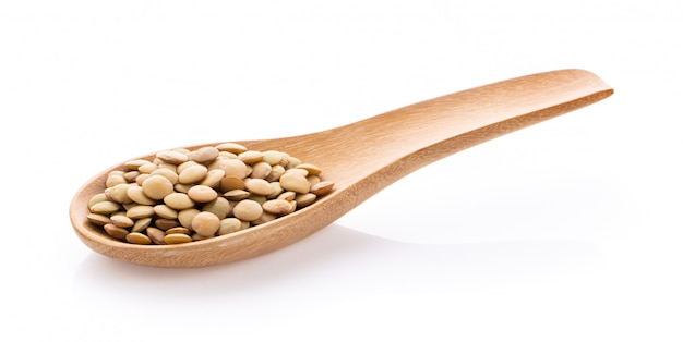 Lentils in wood spoon on white