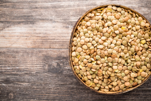 Lentils on wooden background.