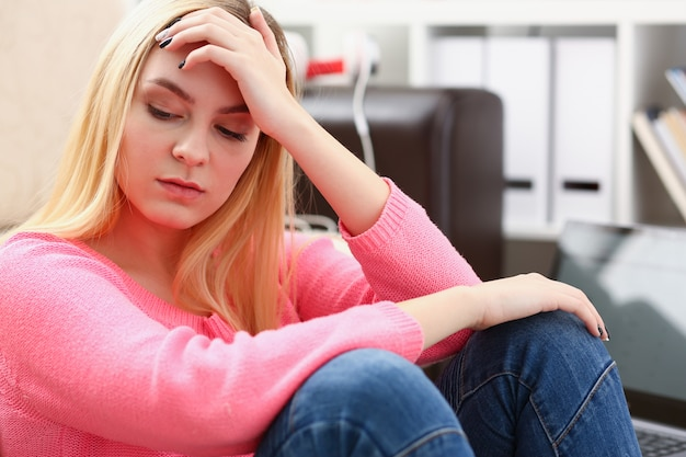 Leonely depressed woman sitting on the couch