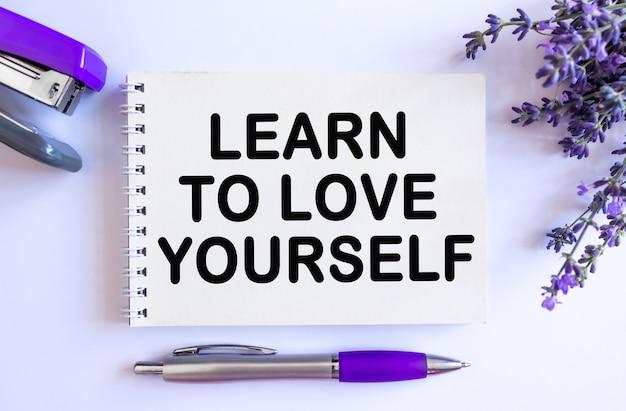 あなた自身を愛するために。白い背景にラベンダーの花束と開いた空白のメモ帳の上面図
