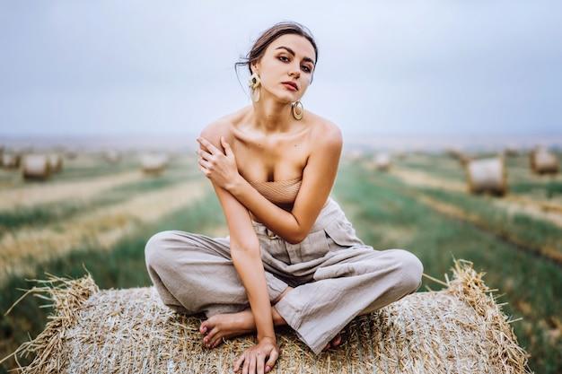 暖かい秋の日に干し草のlesの上に座っているリネンパンツと裸の肩の裸足ブルネット。探している女性。彼女の後ろは麦畑です