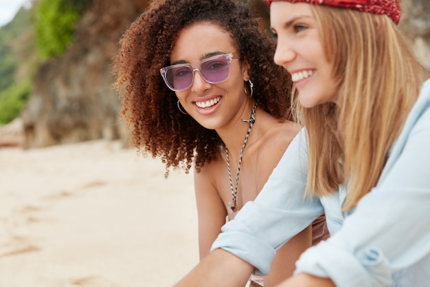 Lesbian couple or close young female friends have vacation on tropical beach, look at sunlight with pleased expression, have true love story.