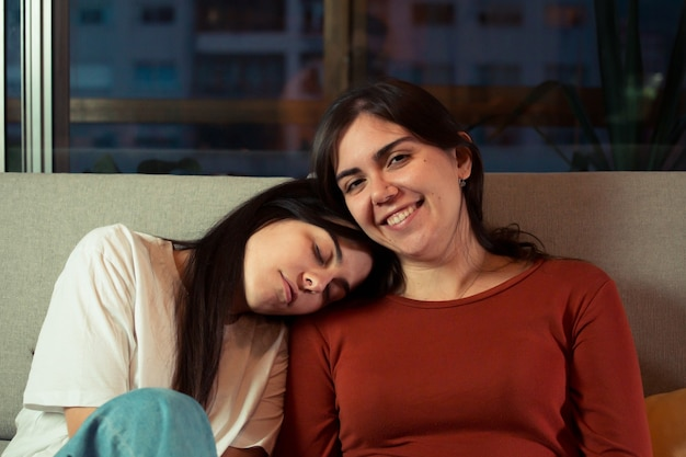 Lesbian couple on the couch smiling on a modern flat