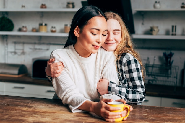 Lesbian couple embracing in kitchen