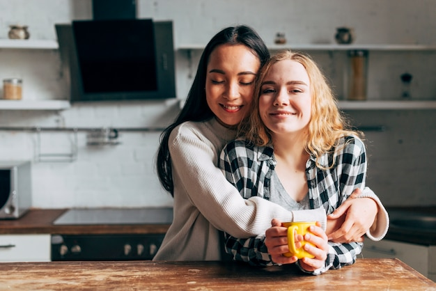 Lesbian couple embracing while drinking tea on kitchen