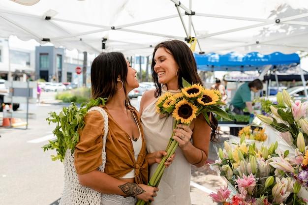 현지 시장에서 꽃 쇼핑을 하는 레즈비언 커플