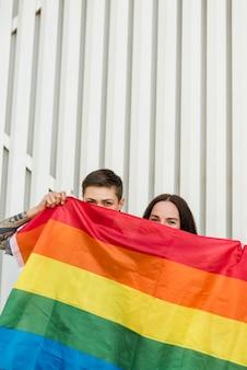 Lesbian couple hiding behind lgbt flag