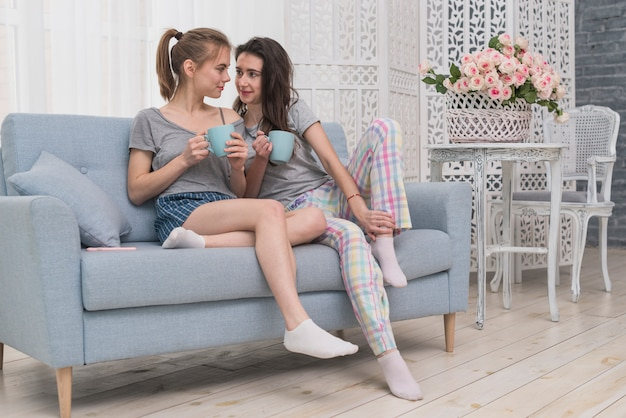 Lesbian couple holding cup of coffee sitting on sofa looking at each other
