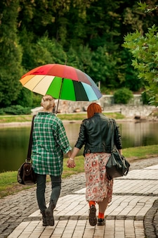 Lesbian couple holding hands walk in the autumn park in the rain with a rainbow umbrella.