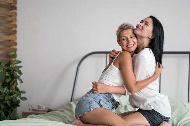 Лесбийская пара обнимается, сидя в постели
