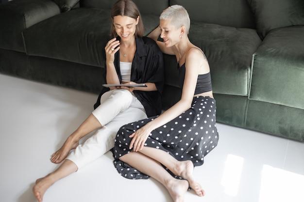 Лесбийская пара смотрит на цифровой планшет, вместе отдыхая возле дивана дома. гомосексуальные отношения и концепция цифрового образа жизни
