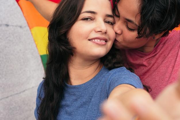 公園でデート中に自分撮りのために愛情を込めてキスするレズビアンカップル