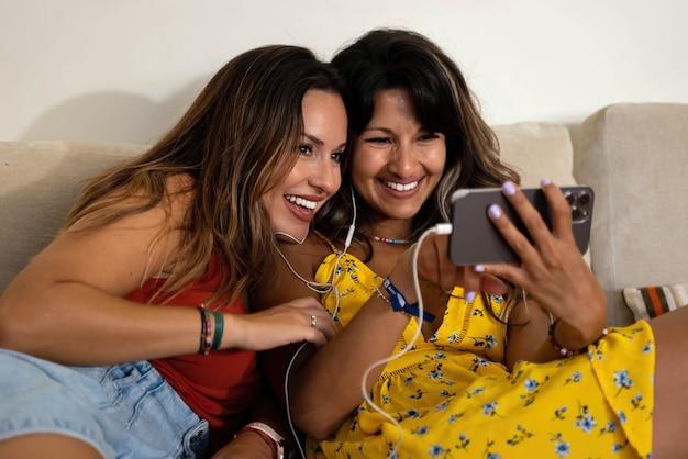 비디오 통화를 하고 휴대폰을 보고 있는 레즈비언 커플
