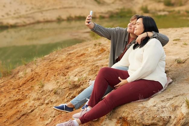 自然の丘の上に座って携帯電話で自分撮りの肖像画を作るレズビアンカップル