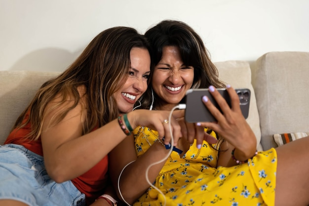 Lesbian couple making a video call and watching mobile phone