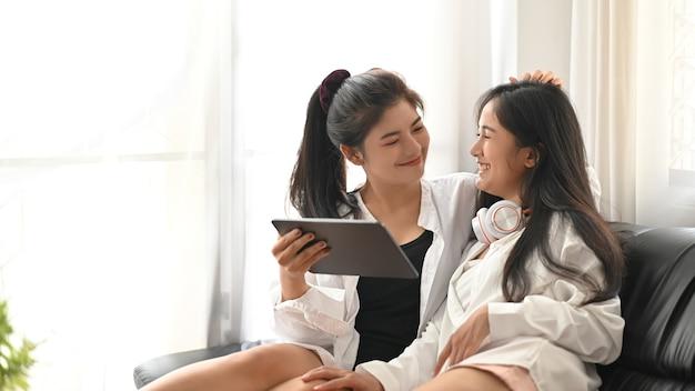 Лесбийская пара отдыхает с планшетом компьютера, сидя вместе на диване