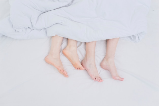 Lesbian couple's feet out of blanket over the bed