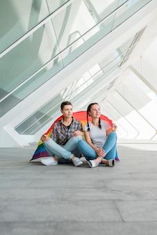 Lesbian couple sitting on paving stone