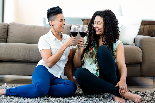 Lesbian couple sitting on rug and toasting wine glasses