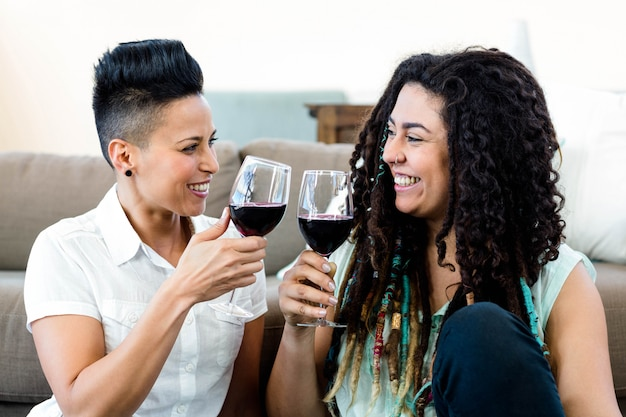 Lesbian couple smiling and toasting wine glasses