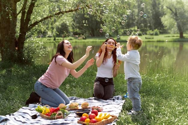 彼らの子供と一緒に時間を過ごすレズビアンのカップル