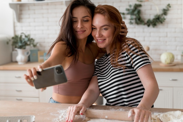 キッチンで自分撮りをしているレズビアンカップル
