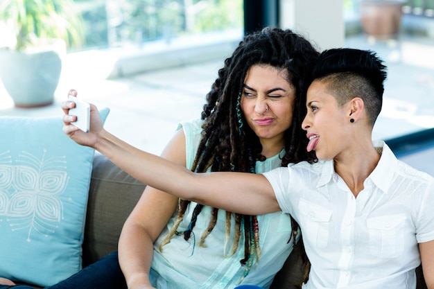 Lesbian couple taking a selfie on phone in living room