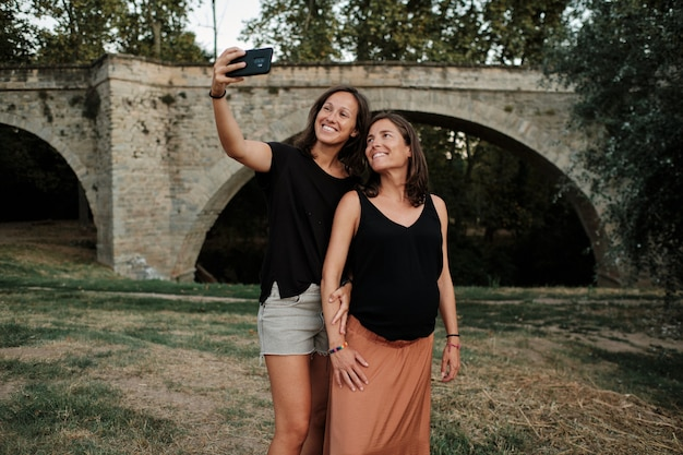 Lesbian couple taking a selfie together in a park