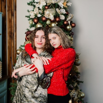 Lesbian couple together indoors cheerfully communicate, preparing for the celebration of christmas.