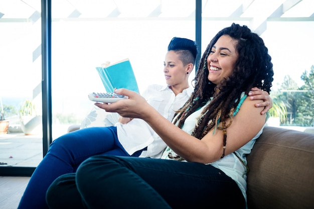 Lesbian couple watching television and reading a book in living room