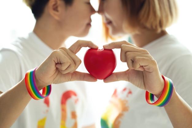 Лесбийская пара в радужном браслете держит красное сердце