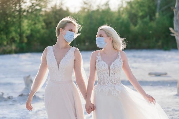 Свадьба лесбийской пары на белом песке в масках для предотвращения эпидемии covid-19