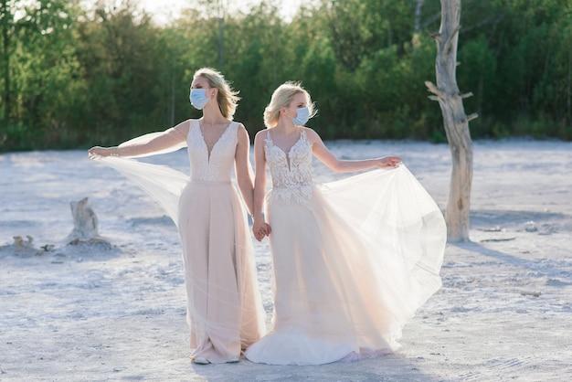 Lesbian couple wedding on white sand, wear masks to prevent epidemic covid-19