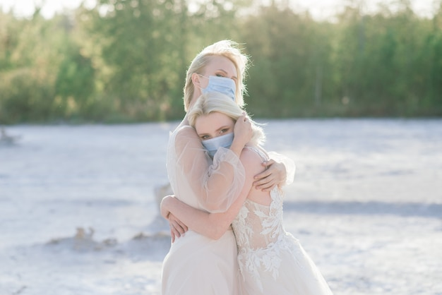 Lesbian couple wedding on white sand, wear masks to prevent epidemic covid-19