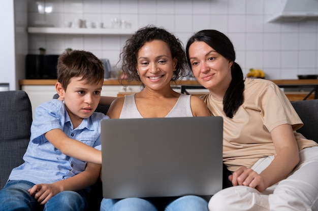 Lesbian couple with their son looking on a laptop