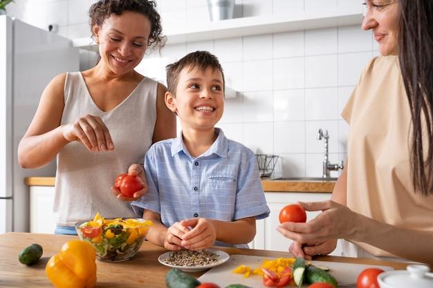 Coppia lesbica con il figlio che prepara del cibo