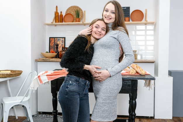 レズビアン妊娠。 2人の幸せな若い女性、そのうちの1人は妊娠していて、台所で食事を作っています。彼女のガールフレンドが野菜を切って、彼女のパートナーの肩に手を置いているのを見ている妊婦。