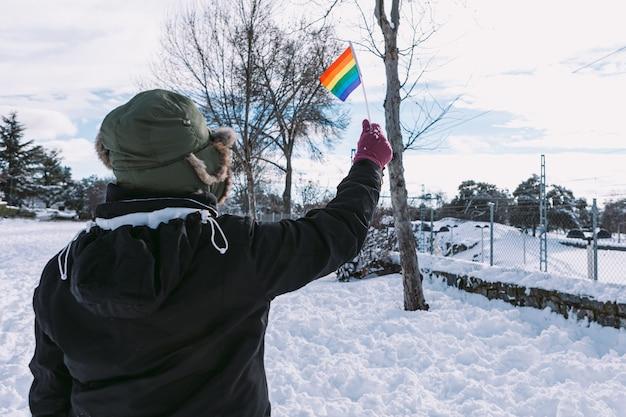 Лесбиянка сзади в снежной шапке для волос в заснеженной местности держит радужный флаг лгбт